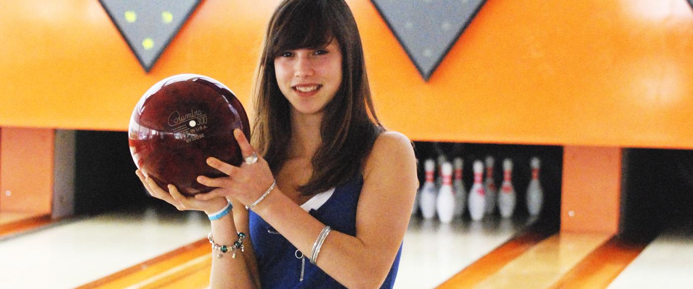 Noia agafant bolo al Bowling-golf Calella